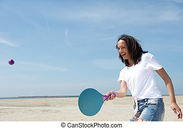 Woman playing paddle ball - Portrait of a young woman...