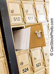 Mail boxes - Rows of gold post office boxes with one open...
