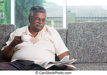 Indian senior adult drinking coffee while reading news paper...