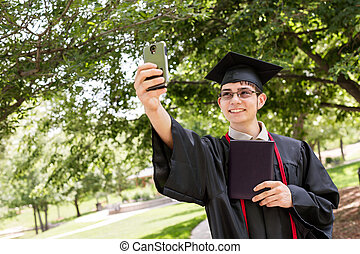 Highschool graduate after graduation caremony in the park.