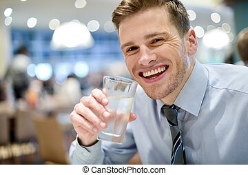 Smiling young man drinking water in restaurant - Handsome...