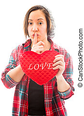 Young woman holding heart shape with a finger on lips