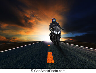 young man riding motorcycle in asphalt road curve with rural...