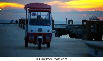 Golf car rides on the pier at sunset and a couple love sitting watching Sunset. Video