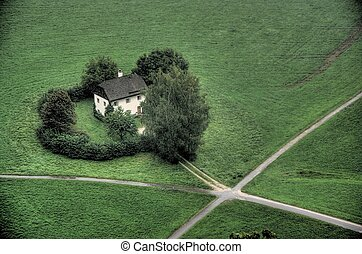 Lonely house - House on grassy hill at crossroads