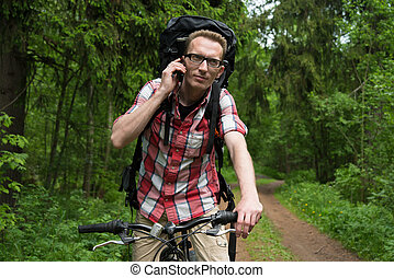 young man on a bicycle talking in the forest on a mobile...