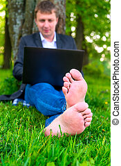 focus on bare feet on the lawn of a businessman