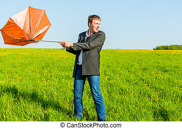 strong wind wrenched orange umbrella man