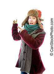 Young woman in warm clothing and pointing back - Young adult...
