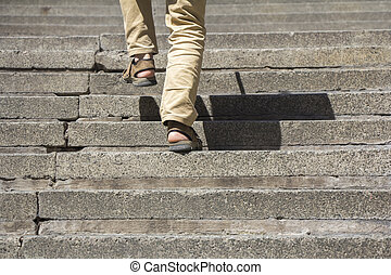 Climbing up stairs - Man climbs on a concrete stairs