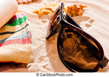 sunglasses and beach accessories on dry fine sand