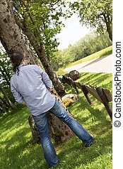 back view of a peeing man in the nature - back view of a...
