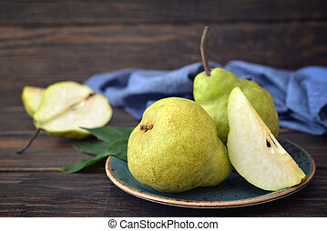 Fresh pears on plate over wooden background closeup