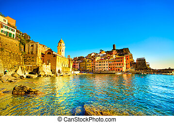 Vernazza village, church, rocks and sea harbor on sunset. Cinque