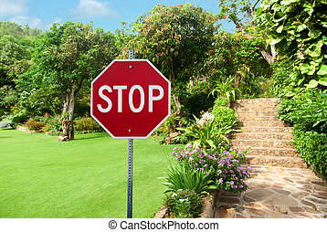 Stop sign against Natural stone landscaping in home garden with