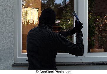The burglar trying to break into someones home