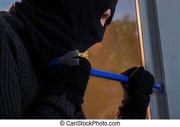 Burglar trying to break into the building. - Burglar in...