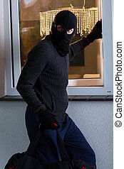 Burglar looks around and opening a window - Burglar in black...