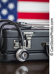 Briefcase and Stethoscope Resting on Table with American...