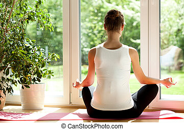 Woman doing yoga at home - Horizontal view of a woman doing...