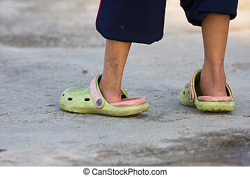 little boy wearing man's green rubber slippers