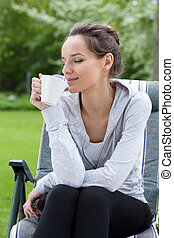 Relaxation with coffee in a garden, vertical