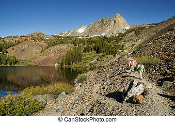 Hiking Past Lake - a couple hiking past Blue Lake in the...