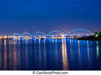 Riga - Illuminated railway bridge across the river Daugava,...