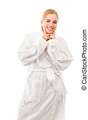 Young woman standing in bathrobe and showing smiley face -...