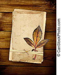 Old cards on wooden planks - Old cards and dry leaf on...
