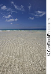 Whispy clouds over paradise - Rippled sand under shallow...