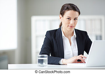Businesswoman in office - Young businesswoman typing and...