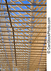 Roof trusses - Wooden roof trusses against a blue sky