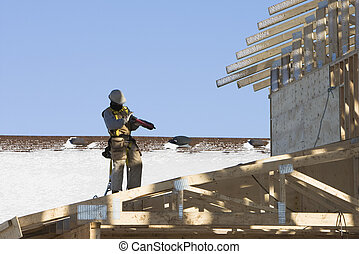 Roofer loading his nailgun - Roofer working on a cold Winter...