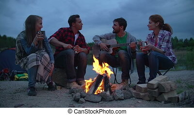 Guys Campout - Four guys sitting by fire wrapped in rug, one...