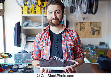 Selling footwear - Portrait of a handsome man selling...