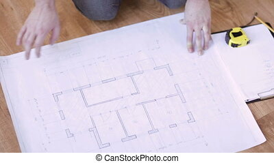 close up of male hands measuring blueprint - repair,...