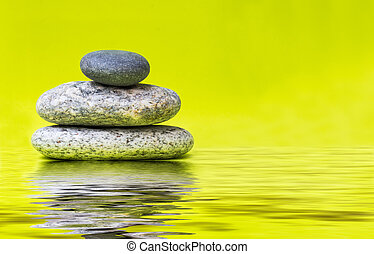 Pebbles - marble coloured stones on a green background with...