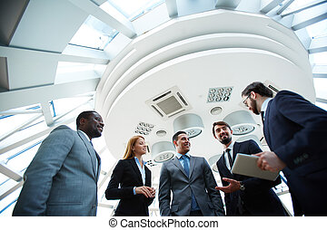 Business conversation - Group of business people discussing...