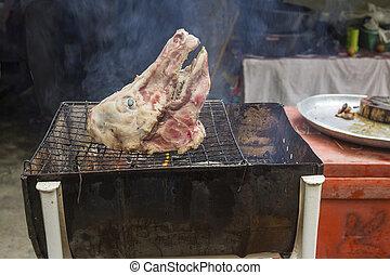 Roast pig's head on grill