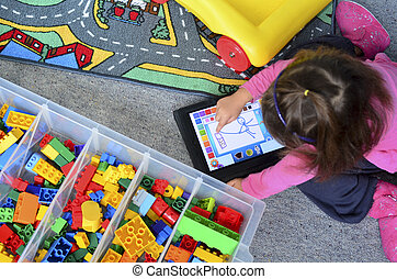 Little girl plays with iPad - AUCKLAND - JUNE 02 2014:Little...
