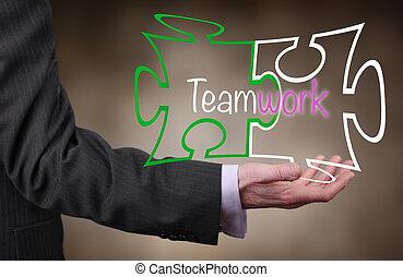 Teamwork - A Businessman holding a Teamwork puzzle concept.