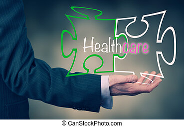 Healthcare - A Businessmans hand holding the words Health...