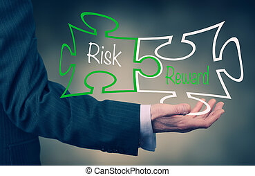 Risk Reward - A Businessmans hand holding the words Risk...