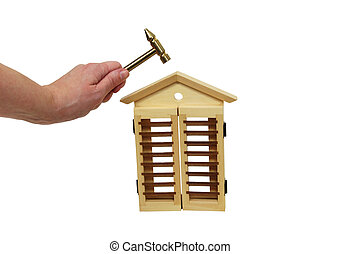 Home repairs - Holding a hammer above a wooden house to...