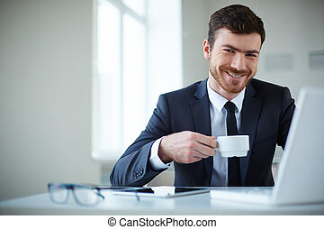 Employer at work - Handsome businessman having tea or coffee...
