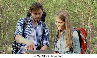 Planning Trip - Tilt up of hiking couple deciding on...