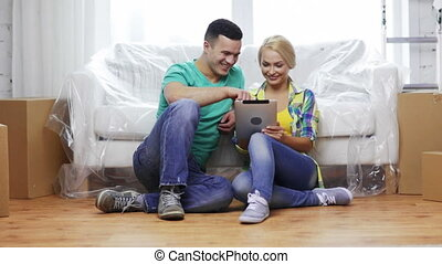 smiling couple with tablet pc in new home - moving, home,...
