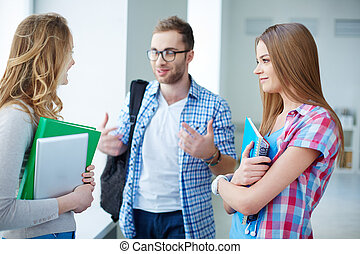Conversation - Portrait of happy teen friends talking during...
