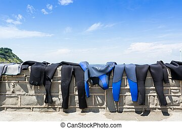Diving suits drying on a brick wall with a sea view